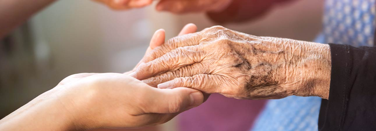 A senior holding hands with their caregiver