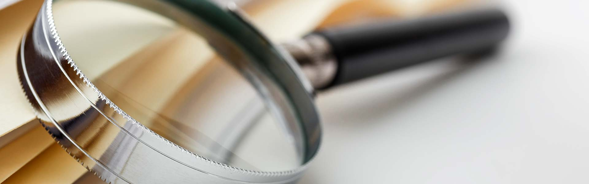 A magnifying glass in front of a pile of papers and folders