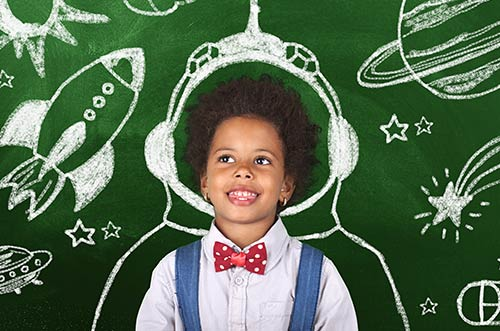 A child in front of a chalkboard with a spaceship and astronaut drawn on it