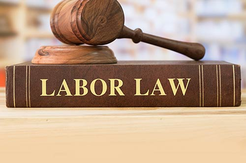 A gavel on top of a book with the title of labor law