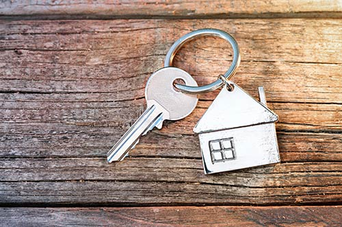 A key ring shaped like a house with a single key on it