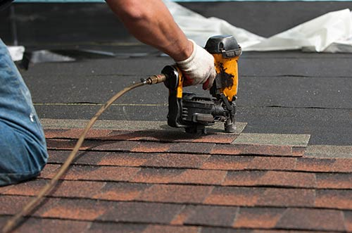 A roofer nailing down a shingle